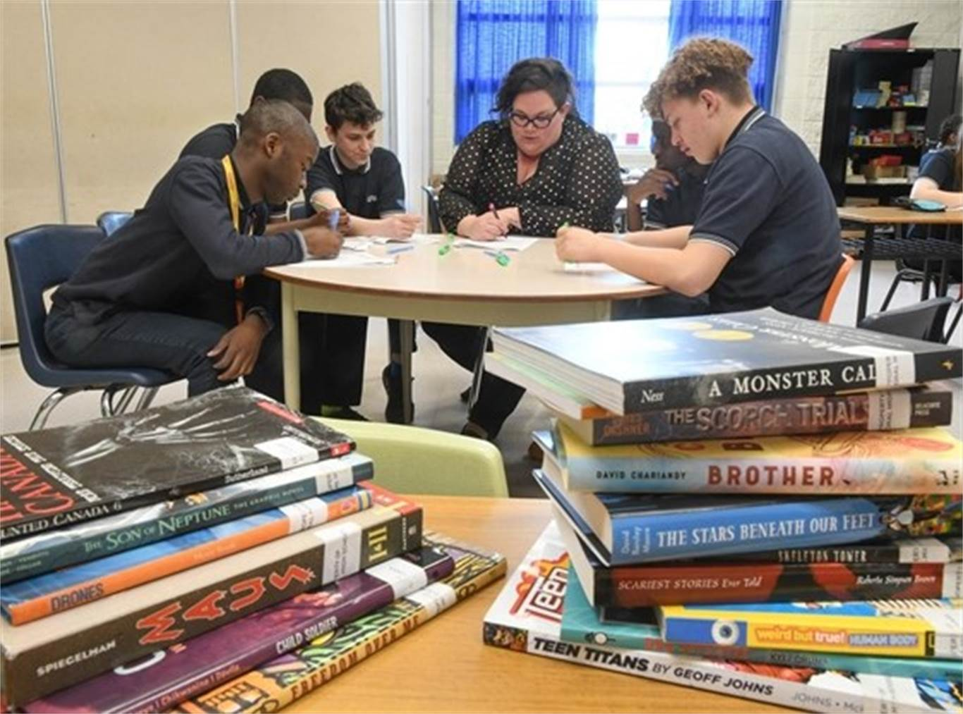 Student success teacher Amanda Ottolino works with Grade 10 students at Cathedral High School. The school created an elective for Grade 10 students called Literacy Skills: Reading and Writing to help students who might be struggling with provincial literacy standards. - Scott Gardner,The Hamilton Spectator